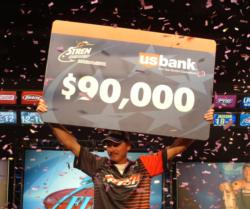 Pro winner Mike Jackson holds up his first-place check worth $90,000.