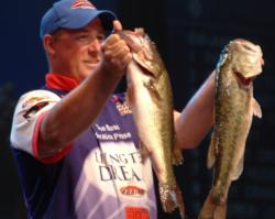 Pro Brian Travis holds up two kicker bass he caught on day one of the Forrest Wood Cup on Lake Murray.