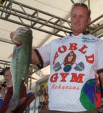 Pro Travis Fox holds up his kicker bass from day one on Kentucky Lake.