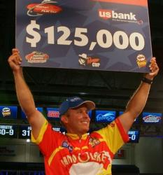 Pro Keith Williams holds up the first-place check worth $125,000.