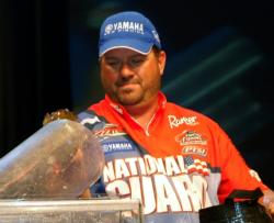 Second-place pro David Curtis places a smallmouth bass on the scale.