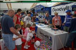 At left, Tim Kist helps his stepson Joshua Bass fish for a prize at the Goodwill booth.