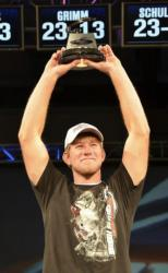 Co-angler Keeton Blaylock holds up his trophy for winning the FLW Tour event on Lake Chickamauga.