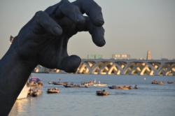 A giant hand from The Awakening frames National Harbor marina during takeoff. The statue, created by J. Seward Johnson, Jr. and originally installed at Hains Point in Washington, D.C. in 1980, was moved to the National Harbor in 2007 after the artist sold the statue for $750,000.