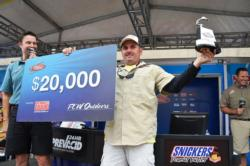 Cory Leonard of Castalia, N.C., proudly displays his first-place check and trophy after winning the FLW Tour co-angler tournament title on the Potomac River.