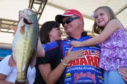 Mark Rose of Marion, Ark., shows off part of his winning 77-pound, 11-ounce catch as his family joins him onstage to celebrate victory at Pickwick Lake.