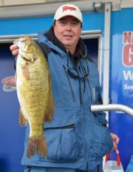 Co-angler leader Greg Scott holds up his biggest bass from day one on Lake Champlain.
