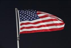 The American flag fluttered steadily in a morning breeze that will lkely strengthen as the day continues.