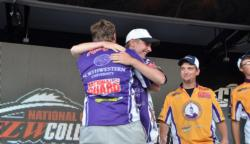 As the second place UW Stevens Point team looks on, Northwestern University teammates Jimmy Morrow and Matthew Kestufskie share an embrace winning the FLW College Fishing Central Regional Championship.
