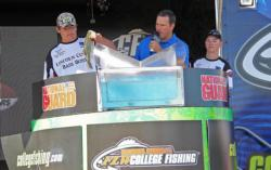 Drew Bailey loads one of the winning fish for Lincoln High School as teammate Adam Diehl looks on.