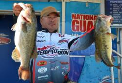 Third-place pro Troy Morrow holds up his two biggest bass from day two on Lake Guntersville.
