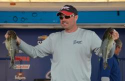 Co-angler champion Hoyt Tidwell holds up his two biggest bass from day three on Smith Lake.
