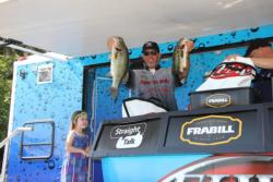 Third-place pro Benjamin Byrd shows off his day-three catch while daughter Chloe looks on with pride.