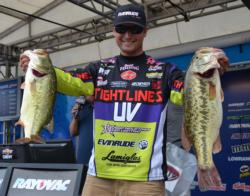 Seventh-place pro Justin Lucas holds up his two biggest bass from day one on Lake Chickamauga.