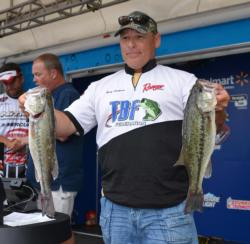 Second-place co-angler Rick Harkness holds up his two biggest bass from day two.