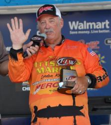 Co-angler champion Jerry Reagan acknowledges the crowd and displays his trophy.