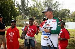 Castrol team pro Mike Surman takes some time out to help children from the local Broward County Boys and Girls clubs hone their fishing skills.