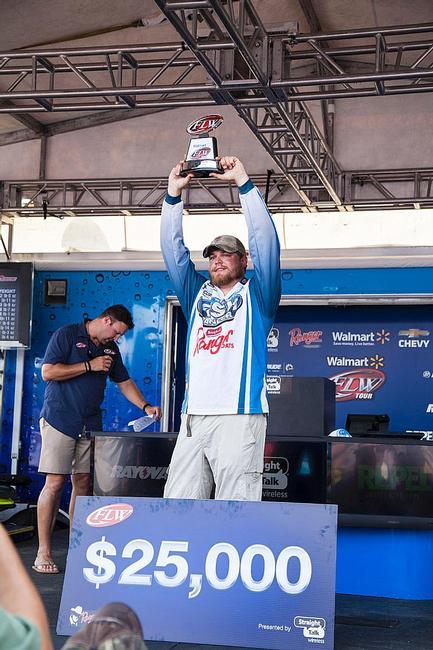 Co-angler champion Braxton Setzer holds aloft his trophy.