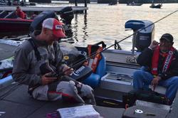 Wesley Strader shares a laugh with his co-angler while rigging up rods for the day.